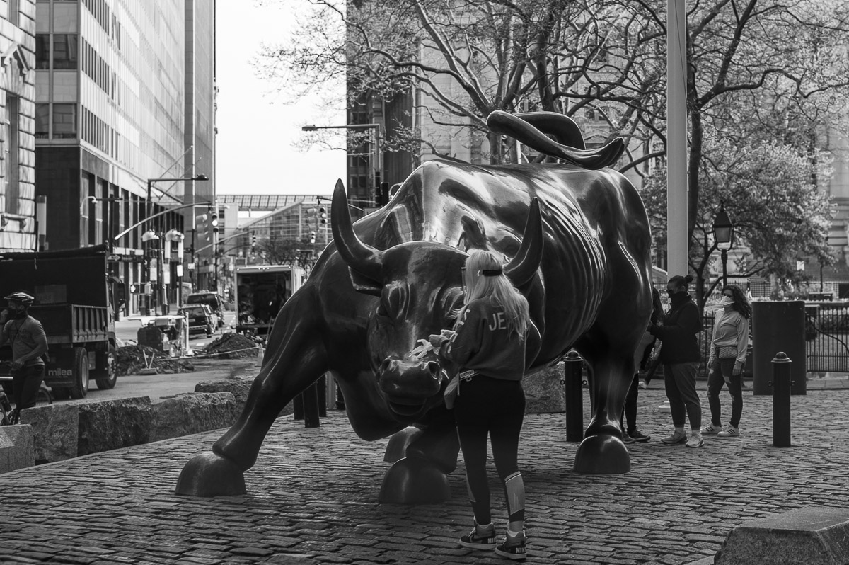 Charging Bull and a woman in gloves and a face shield. Manhattan, New York, during COVID-19. (04/26/2020 by Julie Pavlova Photography)